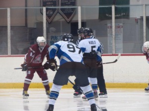 Jared Vuolo taking a faceoff this season for the school ice hockey team.